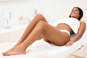 Woman having hair removal procedure on leg applying wax strip