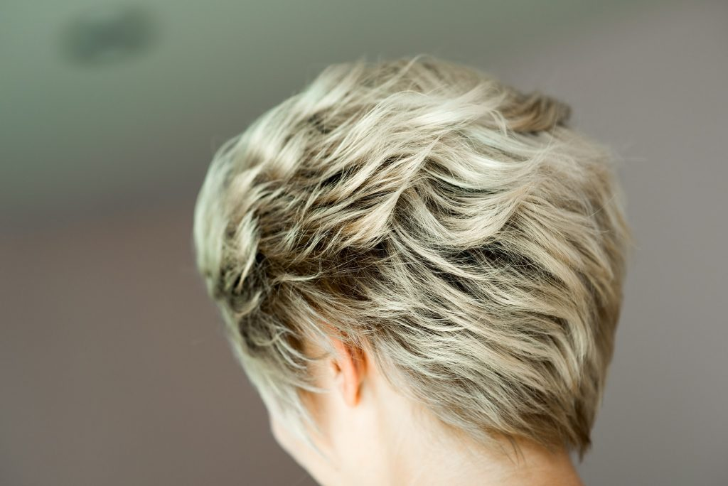 Woman stylist, hairdresser making hairstyle to blonde girl